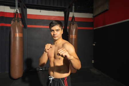 Strong Asian man punching in front of camera, combat punches in boxing sport club workout at training gym fitness center. Exercise indoor sport equipment. People lifestyle. Recreation.