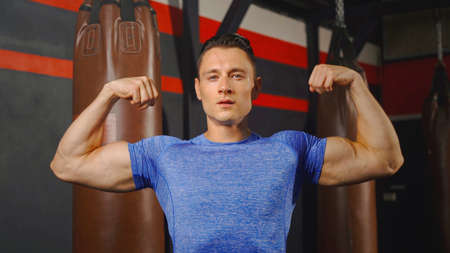 Portrait of strong caucasian man posing muscles in boxing sport club workout at training gym fitness center. Exercise indoor sport equipment. People lifestyle. Banco de Imagens - 167270376