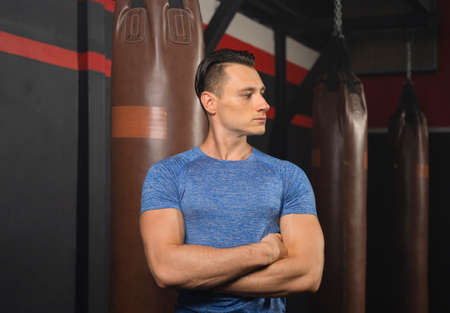 Portrait of strong caucasian man posing muscles in boxing sport club workout at training gym fitness center. Exercise indoor sport equipment. People lifestyle.