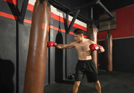 Strong caucasian man punching bag, combat punches in boxing sport club workout at training gym fitness center. Exercise indoor sport equipment. People lifestyle.
