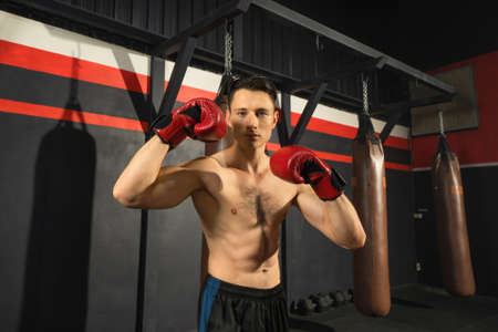 Portrait of strong caucasian man posing muscles, punching combat punches in boxing sport club workout at training gym fitness center. Exercise indoor sport equipment. People lifestyle. Banco de Imagens
