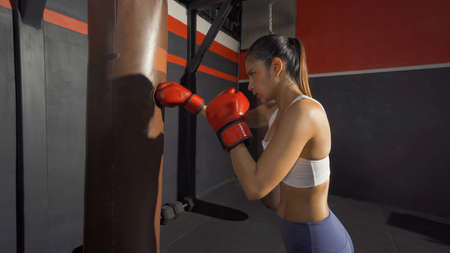 Strong Asian woman punching bag, combat punches in boxing sport club workout at training gym fitness center. Exercise indoor sport equipment. People lifestyle. Banco de Imagens