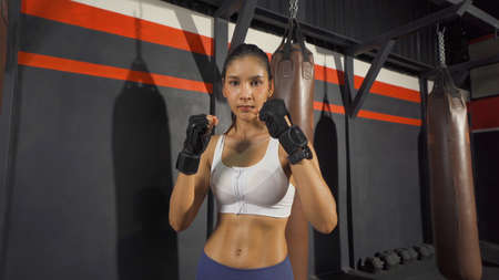 Portrait of strong Asian woman punching in front of camera, combat punches in boxing sport club workout at training gym fitness center. Exercise indoor sport equipment. People lifestyle. Banco de Imagens