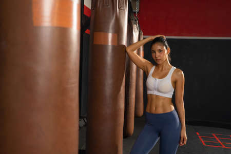 Portrait of strong Asian woman with punching bag, combat punches in boxing sport club workout at training gym fitness center. Exercise indoor sport equipment. People lifestyle. Banco de Imagens - 167270516