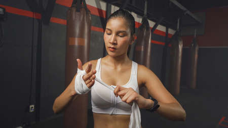 Strong Asian woman doing hand wrapping with a rope, combat punches in boxing sport club workout at training gym fitness center. Exercise indoor sport equipment. People lifestyle. Banco de Imagens - 167270477