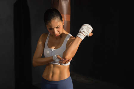 Asian woman injured and painful from an accident. Muscle strength training workout at gym fitness center club. Exercise indoor with sport equipment. Athletic. People lifestyle. Hurt or cramps. Banco de Imagens - 167270478