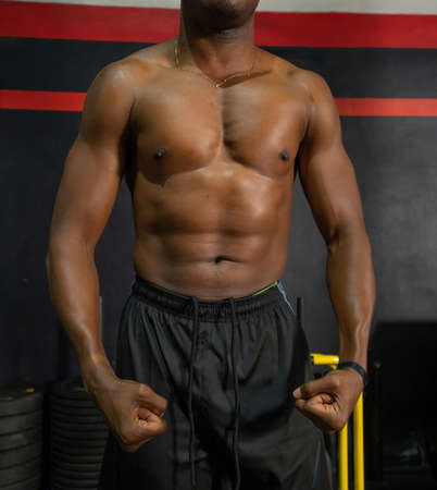 Close up of six pack. Strong black African American boxer man posing muscles in boxing sport club workout at training gym fitness center. Exercise indoor sport equipment. People lifestyle.