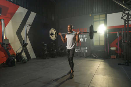 Black African American man lifting sport bar. Muscle strength training workout at gym fitness center club. Exercise indoor with sport equipment. People lifestyle recreation. Banco de Imagens - 167245480