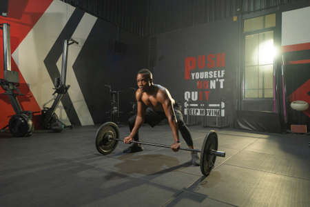 Black African American man lifting sport bar. Muscle strength training workout at gym fitness center club. Exercise indoor with sport equipment. People lifestyle recreation. Banco de Imagens - 167244738