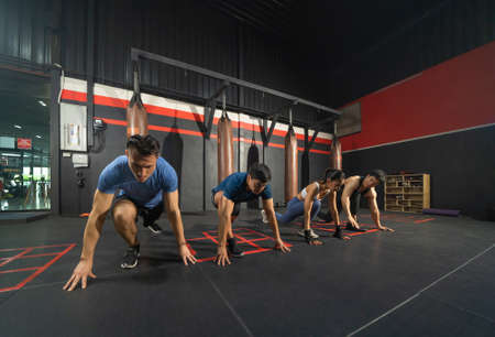 Group of people doing body push up in boxing sport club workout at training gym fitness center. Exercise indoor sport equipment. People lifestyle. Recreation.