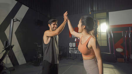 A Caucasian man and Asian woman giving High five at training workout gym fitness center club. Exercise indoor with sport equipment. People lifestyle recreation. Successful team. Banco de Imagens