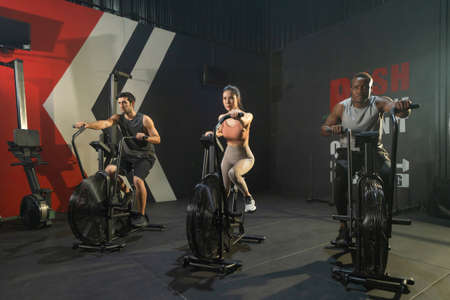 Group of multi ethnic people riding spinning bike or bicycle, Muscle strength training workout at gym fitness center club. Exercise with sport equipment. People lifestyle recreation. Strong team