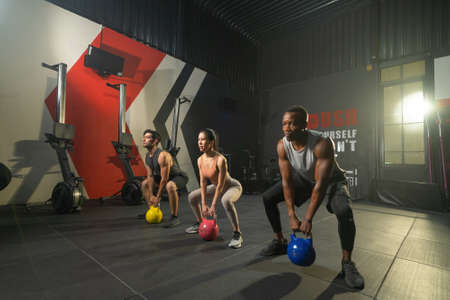 Group of multi ethnic people holding weight kettle bell twist, cardio. Strength training workout at gym fitness center club. Exercise indoor with sport equipment. People lifestyle recreation. Team Banco de Imagens - 167284463