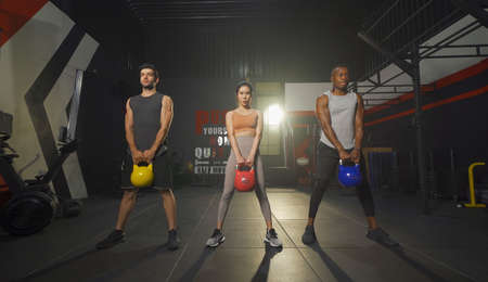 Group of multi ethnic people holding weight kettle bell twist, cardio. Strength training workout at gym fitness center club. Exercise indoor with sport equipment. People lifestyle recreation. Team Banco de Imagens - 167284000