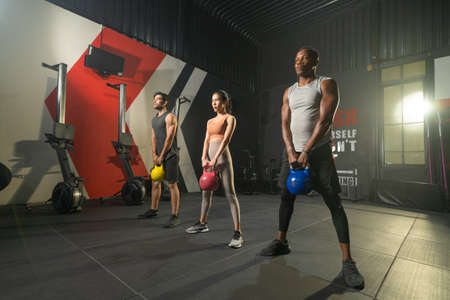 Group of multi ethnic people holding weight kettle bell twist, cardio. Strength training workout at gym fitness center club. Exercise indoor with sport equipment. People lifestyle recreation. Team Banco de Imagens - 167283844