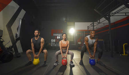Group of multi ethnic people holding weight kettle bell twist, cardio. Strength training workout at gym fitness center club. Exercise indoor with sport equipment. People lifestyle recreation. Team