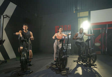 Group of multi ethnic people riding spinning bike or bicycle, Muscle strength training workout at gym fitness center club. Exercise with sport equipment. People lifestyle recreation. Strong team Banco de Imagens - 167284413