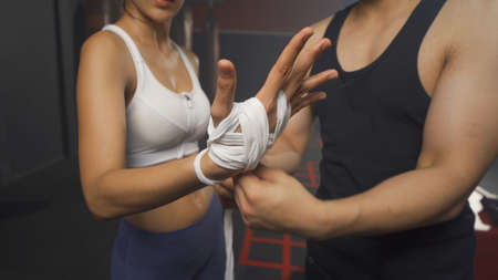 Strong Asian woman doing hand wrapping with a rope with trainer or coach, combat punches in boxing sport club workout at training gym fitness center. Exercise indoor sport equipment. People lifestyle. Banco de Imagens - 167288139