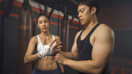 Strong Asian woman doing hand wrapping with a rope with trainer or coach, combat punches in boxing sport club workout at training gym fitness center. Exercise indoor sport equipment. People lifestyle.