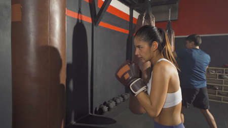 Strong Asian woman punching bag by coach or trainer with team, combat punches in boxing sport club workout at training gym fitness center. Exercise indoor sport equipment. People lifestyle.