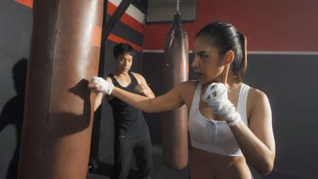 Strong Asian woman punching bag by coach or trainer with team, combat punches in boxing sport club workout at training gym fitness center. Exercise indoor sport equipment. People lifestyle. Banco de Imagens - 167325869