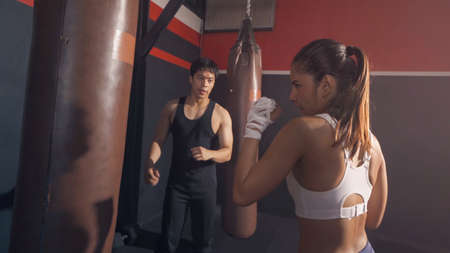 Strong Asian woman punching bag by coach or trainer with team, combat punches in boxing sport club workout at training gym fitness center. Exercise indoor sport equipment. People lifestyle. Banco de Imagens - 167325588