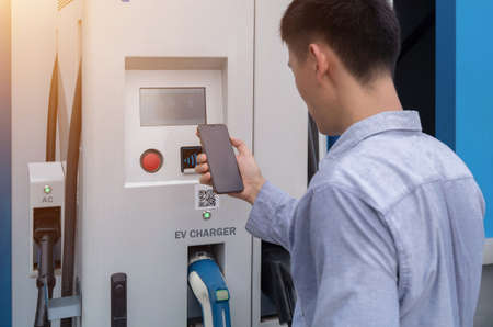 Asian Man using smartphone. EV car charger cable or electric vehicle station. Cable connected at gas station, power supply battery charging eco environment future technology energy innovation. People.