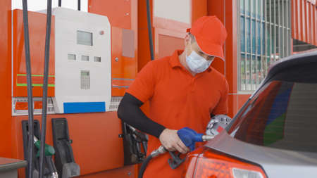 A Caucasian man, people, worker filling up fuel by using petrol pump at gasoline petrol station, wearing a face mask. refuel petroleum oil and energy vehicle business service. Stock Photo