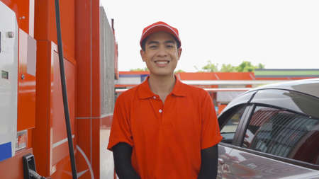Portrait of an Asian man, people, worker on video call conference, filling up fuel by using petrol pump at gasoline petrol station, refuel petroleum oil and energy vehicle business service. Stock Photo