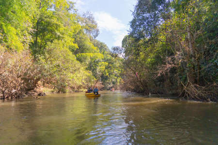 Sailing on lake or river water rafting, paddling on boat canal in park. Sightseeing in forest trees at Mae Sot ,Tak, Thailand. Nature landscape. Tourist adventure activity. Travel in holiday vacation.