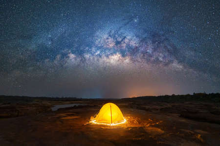 Camping tent under sky on mountain hills with the milky way with bright stars at night in travel on holiday vacation concept. Natural universe space landscape background. Adventure tourist activity. 版權商用圖片