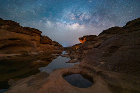 Sam Phan Bok with milky way and stars at night, Ubon Ratchathani, Thailand. Dry rock reef in the Mekong River with mountain hills. Nature landscape background. Grand Canyon of Thailand.