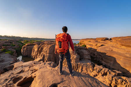 Back of tourist man, a backpacker people, travel in Sam Phan Bok, Ubon Ratchathani, Thailand. Dry rock with mountain hills. Nature landscape. Grand Canyon of Thailand. Adventure lifestyle activity. 版權商用圖片
