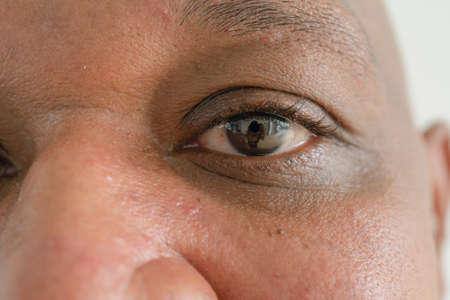 Close up of Black African American elderly black man eyes. Texture of the black eye is visible. Macro detail of iris.