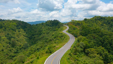 Aerial view of cars driving on curved, zigzag curve road or street on mountain hill with green natural forest trees in rural area of Nan, Thailand. Transportation.