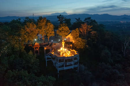 Aerial view of golden buddha pagoda stupa. Wat Phrathat Khao Noi Temple Park, Nan, Thailand with green mountain hills and forest trees. Thai buddhist temple architecture. Tourist attraction at night.