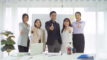 Portrait of a group of smiling Asian business people meeting thumbs up, discuss documents, and working in a meeting room in office seminar, present ideas with colleagues. Corporate teamwork Banco de Imagens