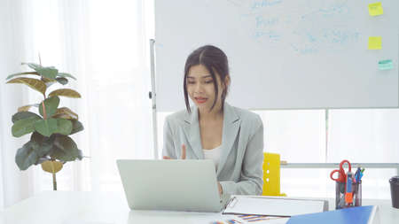 Portrait of a business Asian woman, Thai person talking to colleagues in webcam group video call conference online from home with computer laptop, technology device in quarantine. Banco de Imagens