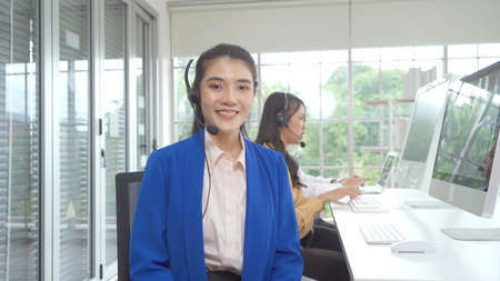Group of Asian business women. People talking and working call center online in office with headset and computer on webcam video call conference. Executive partner agent team. Customer support service