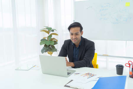 Portrait of business Asian man, Thai person talking to colleagues in webcam group video call conference online from home with computer laptop, technology device in quarantine. Banco de Imagens