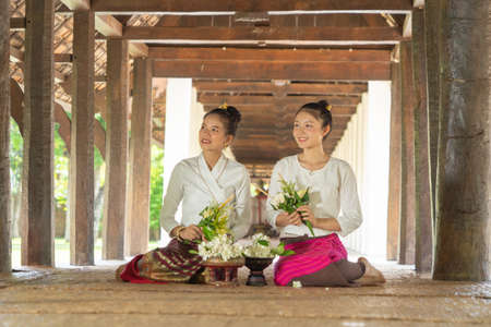 Portrait of group of Asian Shan women girls, Tai Yai, northern Thai people with traditional Lanna clothes holding flowers at Wat Ton Kwen temple, lanterns decoration. Culture lifestyle. Banco de Imagens