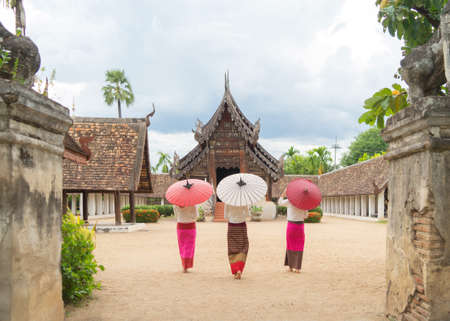 Portrait of group of Asian Shan women girls, Tai Yai, northern Thai people holding an umbrella with traditional Lanna clothes at Wat Ton Kwen temple, decoration. Culture lifestyle.
