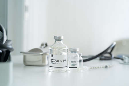 COVID-19 vaccine bottles with syringe injection needle on table, Coronavirus vaccination medical treatment and healthcare instruments in lab or laboratory in technology chemistry.