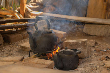 Old teapot for boiling water by using traditional kettle and fire, water heater at wooden kitchen at local home. People lifestyle.
