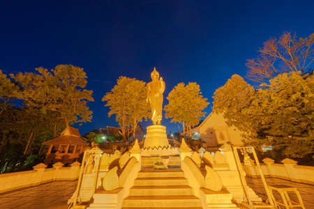 Golden buddha pagoda stupa. Wat Phrathat Khao Noi Temple Park, Nan, Thailand with green mountain hills and forest trees. Thai buddhist temple architecture. Tourist attraction at night.