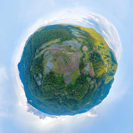 Little planet 360 degree sphere. Panorama of aerial top view of paddy rice terraces with water reflection, green agricultural fields, mountain hills valley, Chiang Mai, Thailand. Nature landscape.