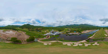 360 panorama by 180 degrees angle seamless panorama of aerial view of Tha Chomphu White Bridge, Lamphun, Thailand with lake or river, forest trees and green mountain hill. Nature landscape. Banco de Imagens