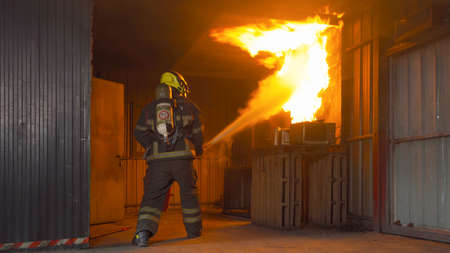 A firefighter or fireman with uniform using water fire hose against hot burning fire and dangerous smoke in the container, an emergency accident rescue. People. Hero