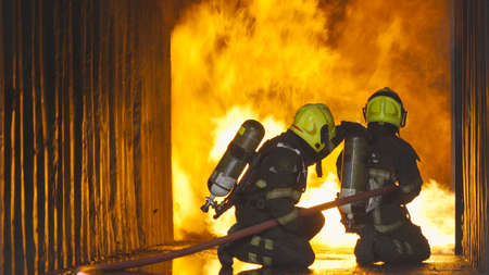 A group of firefighter or fireman with uniform using water fire hose against hot burning fire and dangerous smoke in the container, an emergency accident rescue. People. Hero teamwork. Banco de Imagens