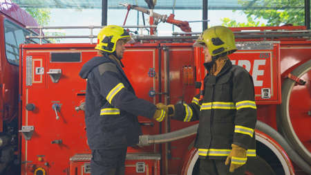 A successful group of caucasian firefighters or firemen team with uniform shaking hands, working on their career. An emergency accident rescue. People. Hero teamwork with a fire truck car. Service job
